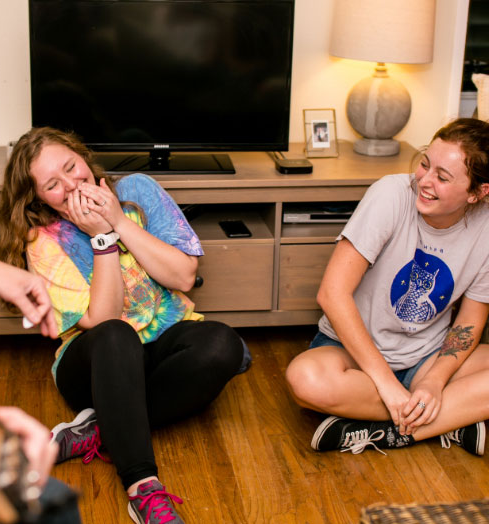 Two laughing housing students sitting on the floor.