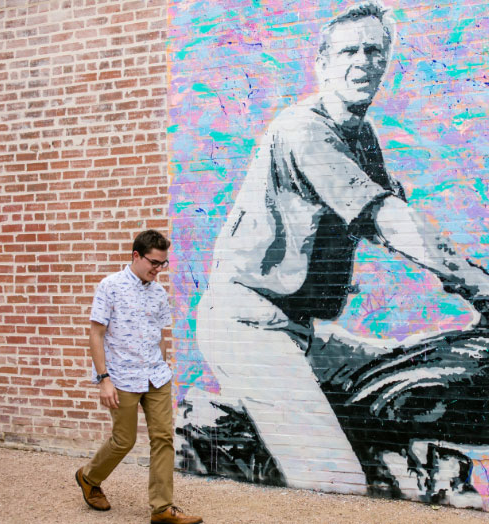 A student in Deep Ellum walking in front of a mural painted on a brick wall.