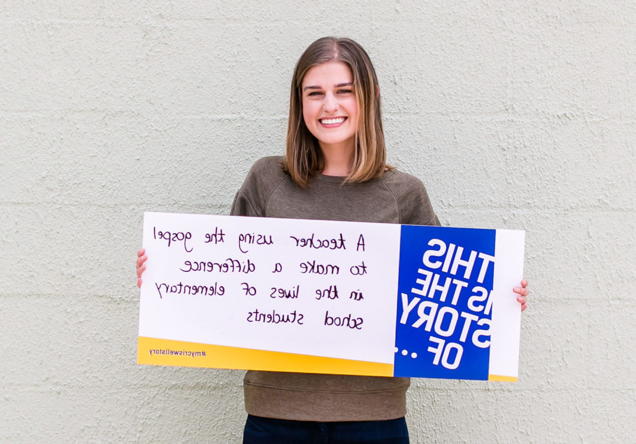 "A female undergraduate displaying a sign that states, ""This is the story of a teacher using the gospel to make a difference in the lives of elementary school students."""