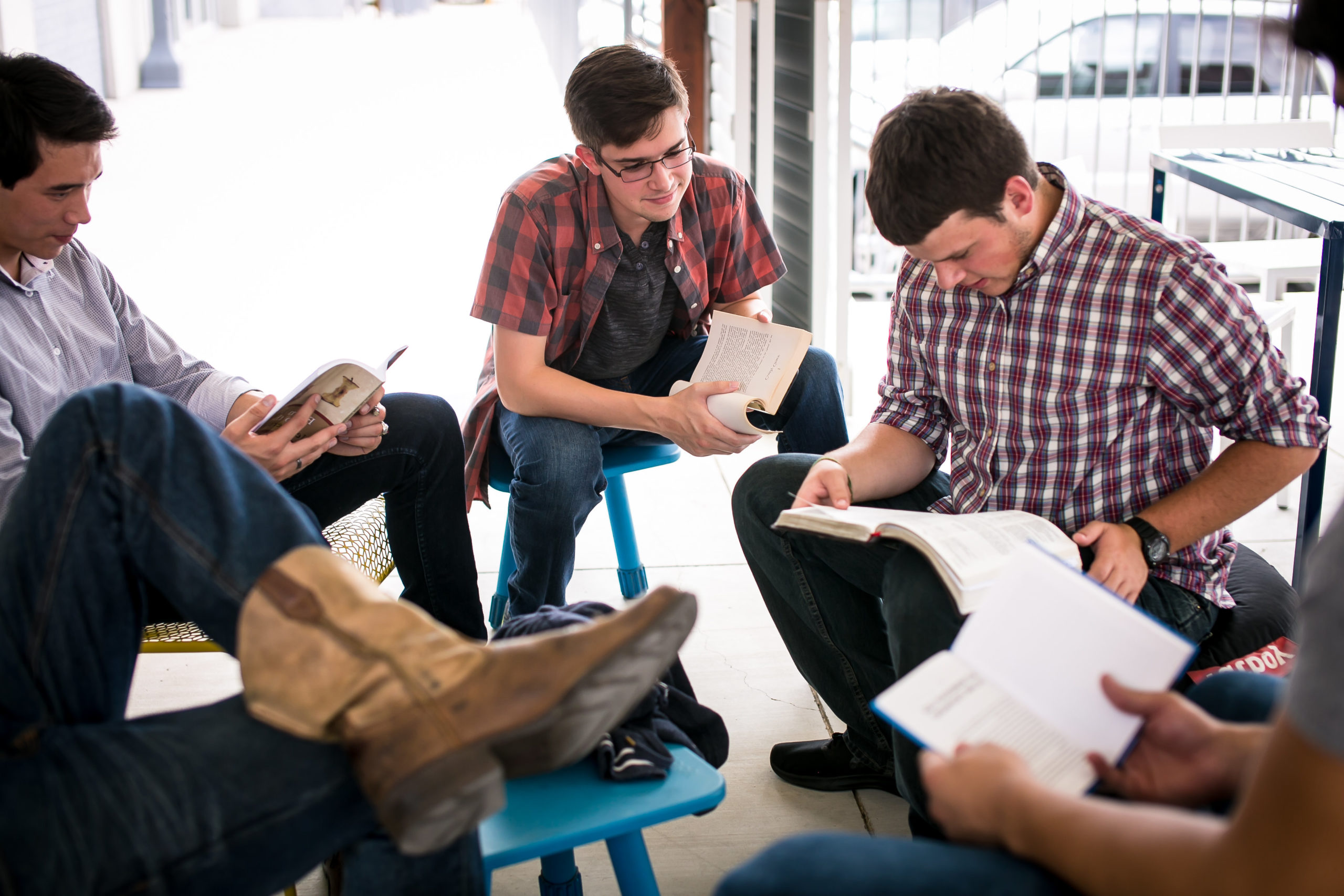 A small group of young men participating in a Bible study at a local establishment.