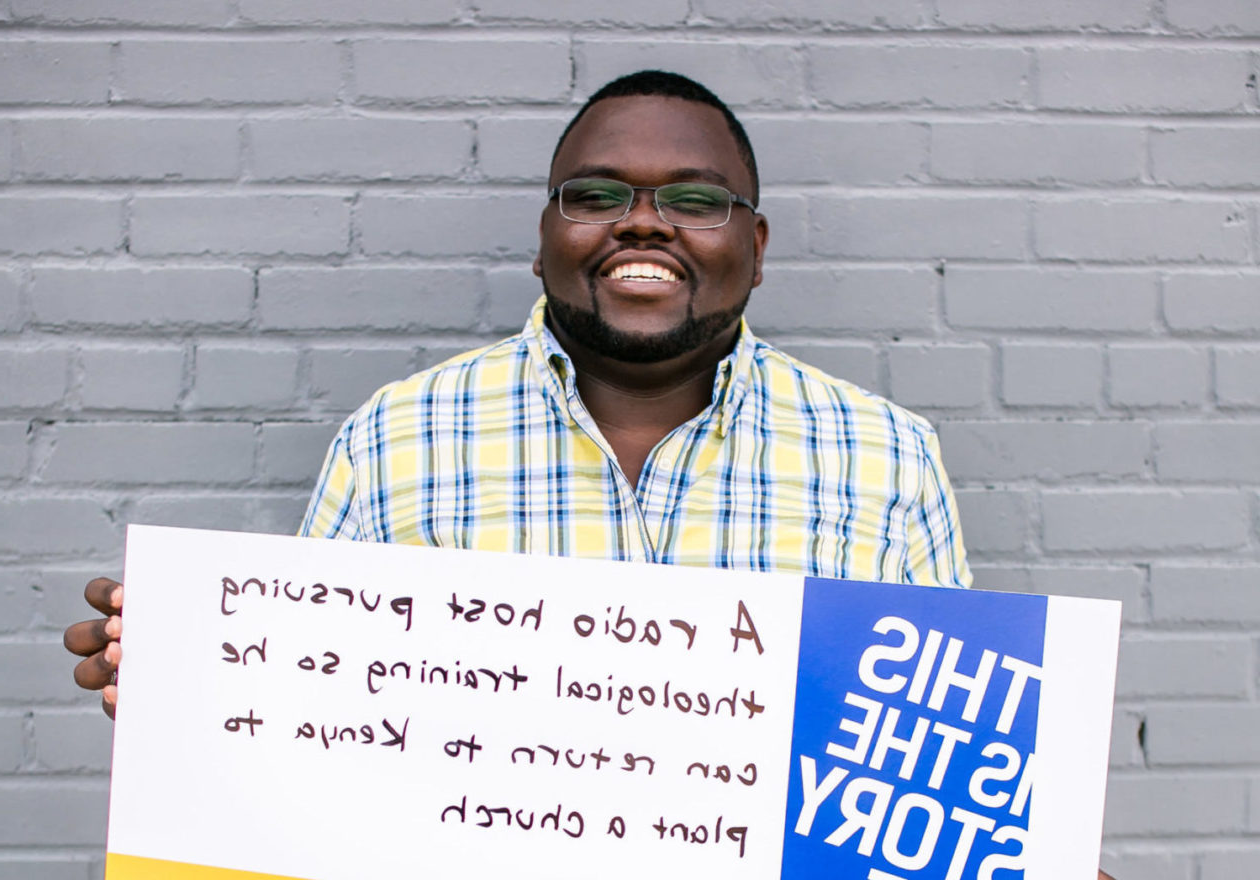 "A smiling graduate student holding a sign that reads, ""This is the story of a radio host pursuing theological training so he can return to Kenya to plant a church."""